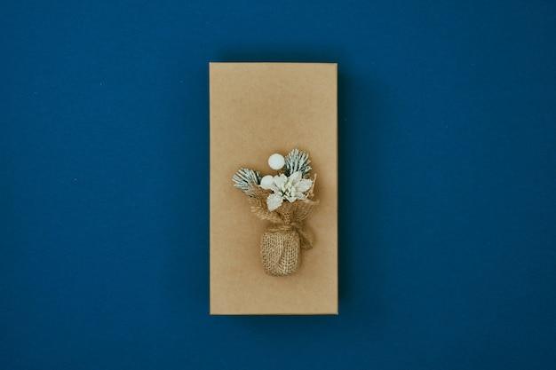 Boeket gedroogde bloemen op een geschenkdoos op een blauwe achtergrond new years decor kopieer ruimte plat lag mock up bovenaanzicht