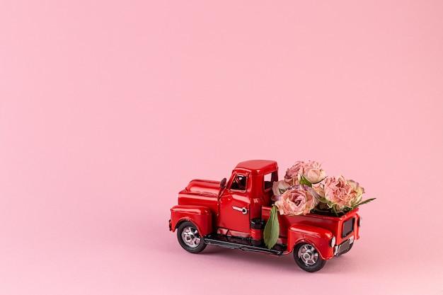 Boeket gedroogde rozen in de achterkant van een speelgoed vrachtwagen.