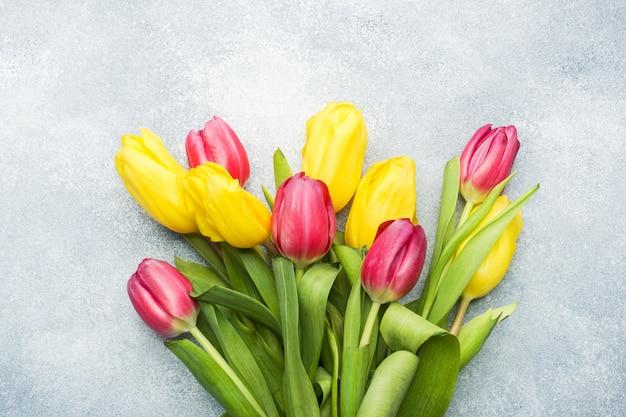 Boeket gele en roze tulpen op lichtblauw. copyspace