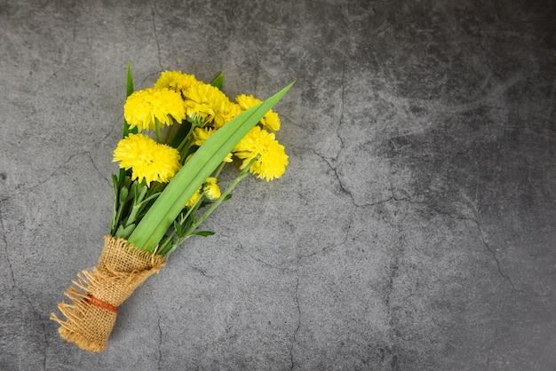 Boeket gele mum bloemen lente en pandan verpakt in zak op donkere plaat achtergrond