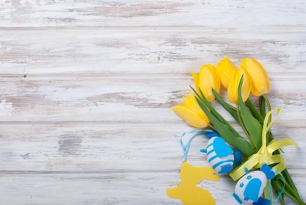 Boeket gele tulpen en chikken paaseieren met een blauw lint op een hout