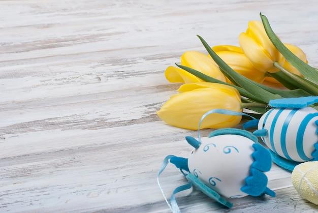 Boeket gele tulpen en chikken paaseieren met een blauw lint op een houten achtergrond