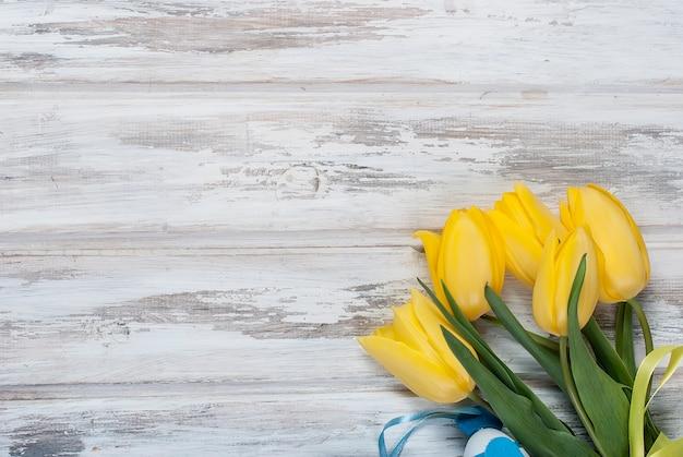Boeket gele tulpen en een geschenk met een blauw lint op een hout