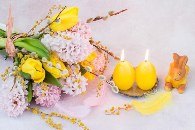 Boeket gele tulpen en roze hyacinten met wilg en mimosa, een konijn en twee kaarsen in de vorm van eieren