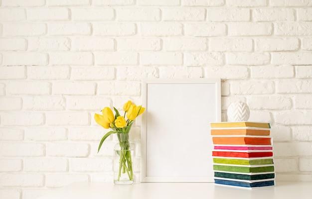 Boeket gele tulpen in een glazen vaas, stapel kleurrijke boeken en blanco fotolijstjes op een witte bakstenen muur achtergrond. mock-up ontwerp