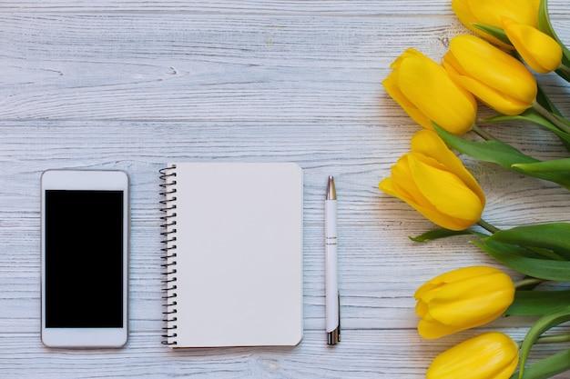 Boeket gele tulpen, lege laptop, pen en witte slimme telefoon. plat lag, bovenaanzicht.