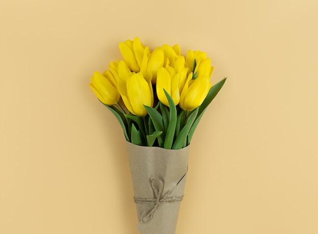 Boeket gele tulpen verpakt in kraftpapier op een beige achtergrond.