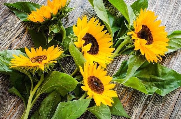 Boeket gele zonnebloemen op vintage gestructureerde houten tafel.
