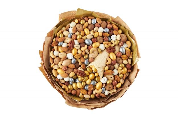 Boeket gemaakt van noten van verschillende kwaliteiten en snoepjes, bovenaanzicht op wit