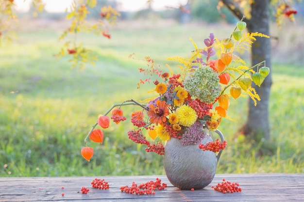 Boeket herfst bloemen in rustieke kruik op houten tafel buiten bij zonsondergang