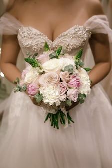 Boeket houden door bruid ze draagt een witte trouwjurk bij de trouwwinkel. foto zonder gezicht