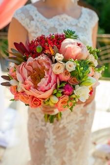 Boeket in de handen van de bruid van verschillende bloemen van pioenrozen en rozen