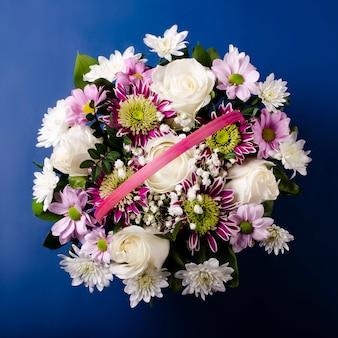 Boeket in een mand bovenaanzicht op een blauwe achtergrond. boeket rozen, chrysanten en gipskruid