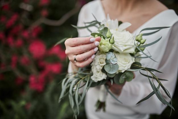 Boeket in handen van de bruid, vrouw klaar voor huwelijksceremonie