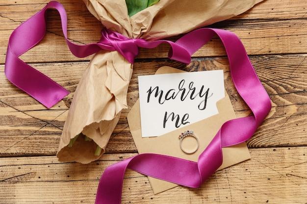 Boeket in kraftpapier met een marry me-kaart en voorstelring op houten tafelblad Premium Foto