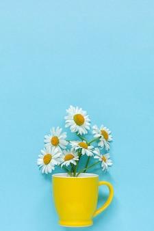 Boeket kamille madeliefjes bloemen in gele mok op pastel blauwe kleur papier