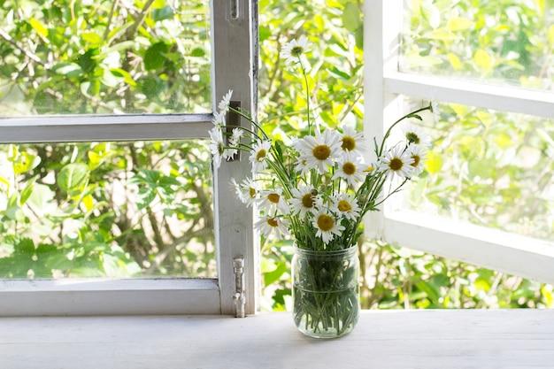 Boeket madeliefjes in pot op vensterbank