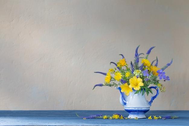 Boeket met blauwe en gele bloemen in theepot op houten tafel