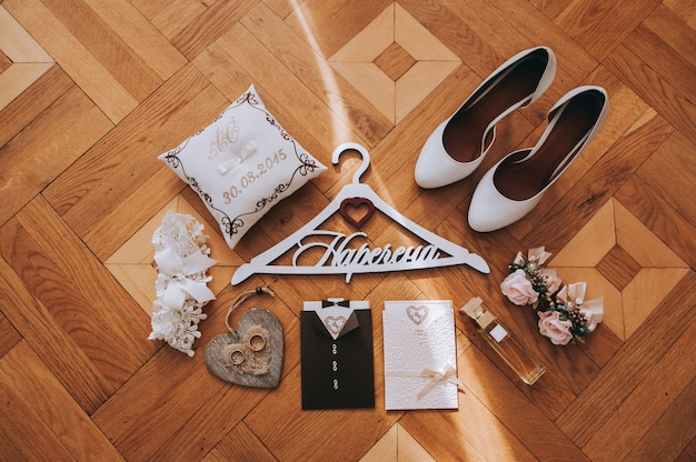 Boeket met pioenen, boutonnieres, parfum, vrouwelijke leren schoenen, papieren kaart en trouwringen
