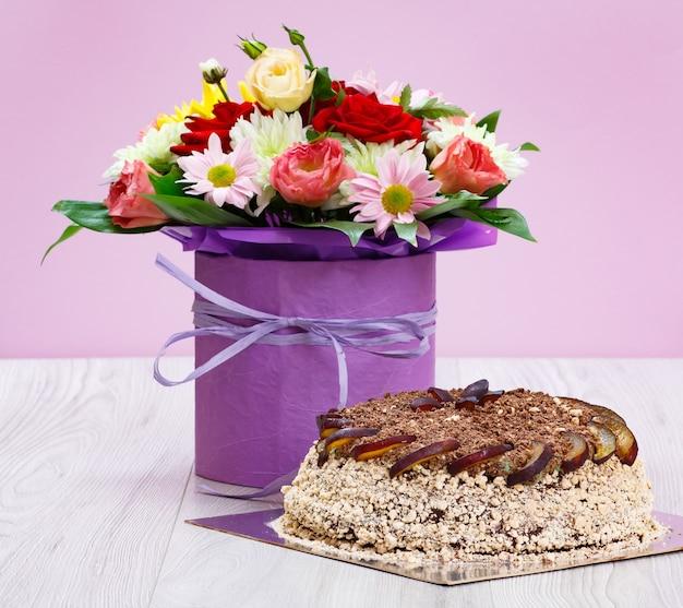 Boeket met wilde bloemen en een chocoladetaart op de houten planken