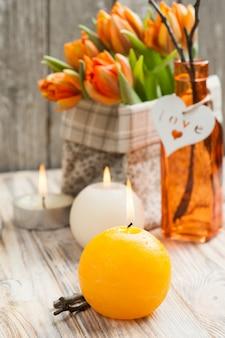 Boeket oranje tulpen, aangestoken kaarsen