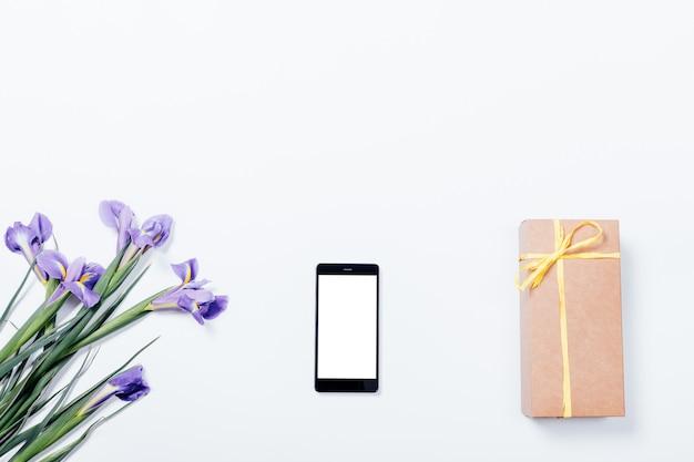 Boeket paarse irissen, mobiele telefoon en geschenkdoos op wit