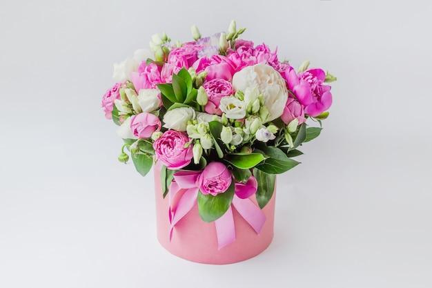 Boeket pioenrozen, rozen in een roze doos