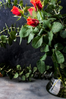 Boeket rode rozen en veel groene bladeren in een vaas op een zwarte achtergrond