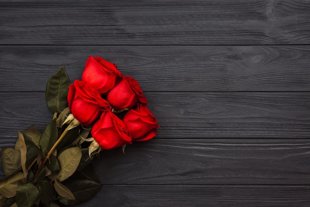 Boeket rode rozen op een donkere houten achtergrond.