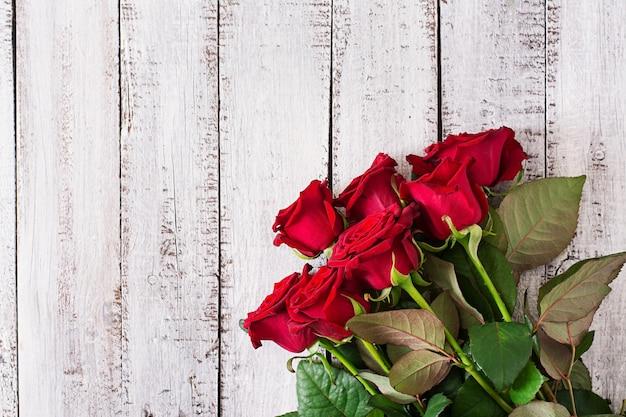 Boeket rode rozen op een houten tafel.