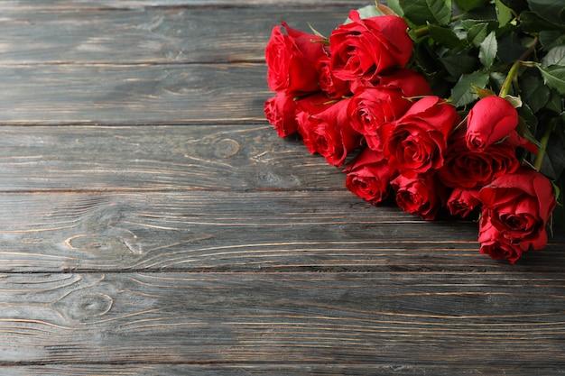Boeket rode rozen op houten achtergrond, ruimte voor tekst