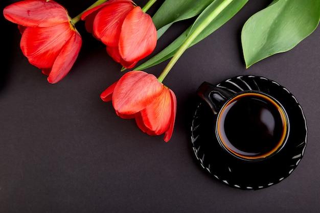 Boeket rode tulpen en kopje koffie