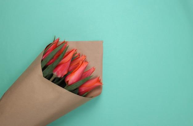 Boeket rode tulpen in papieren verpakking op mint kleur