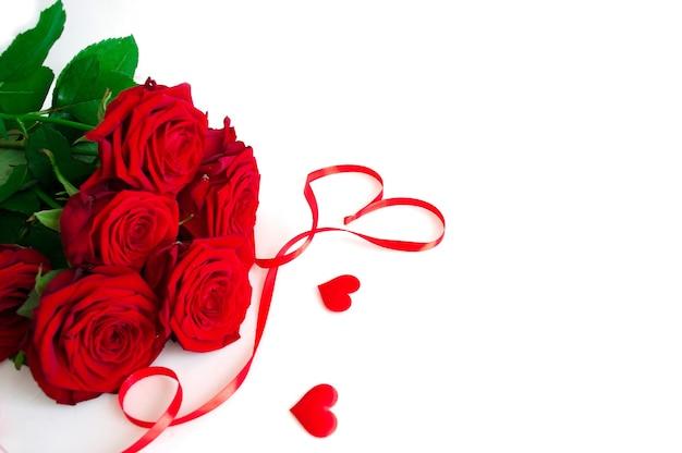 Boeket rode verse rozen geïsoleerd op een witte achtergrond met rood lint. plat leggen. kopie ruimte.