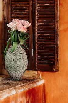 Boeket roze bloemen in een oude grote vaas op een vensterbank