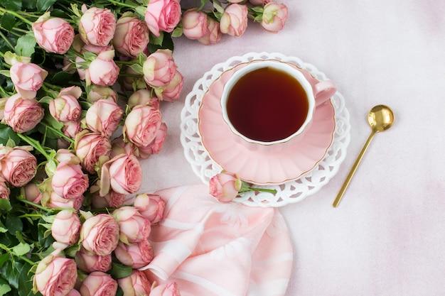 Boeket roze rozen en thee in een kopje