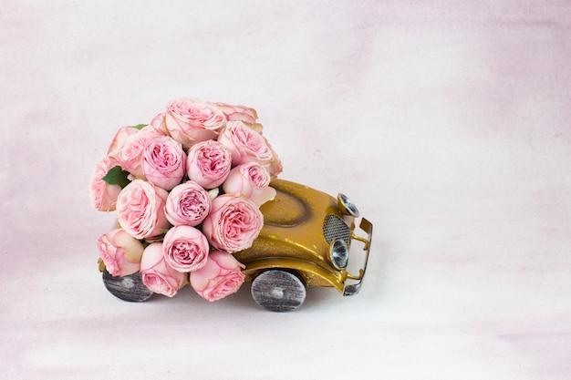 Boeket roze rozen in de auto op een roze achtergrond