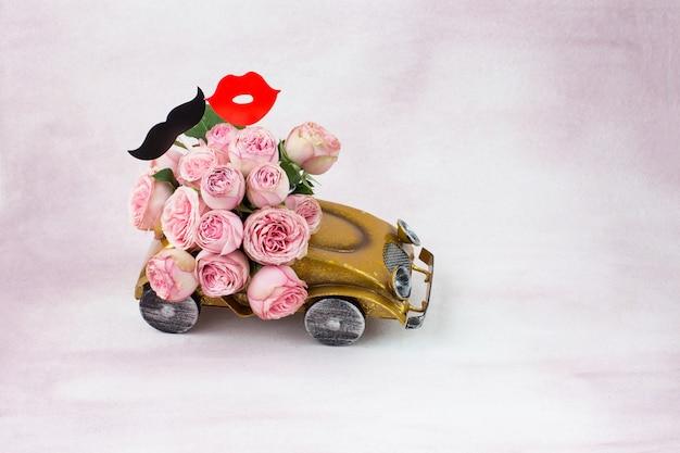 Boeket roze rozen in de auto, stickers: snor en kus