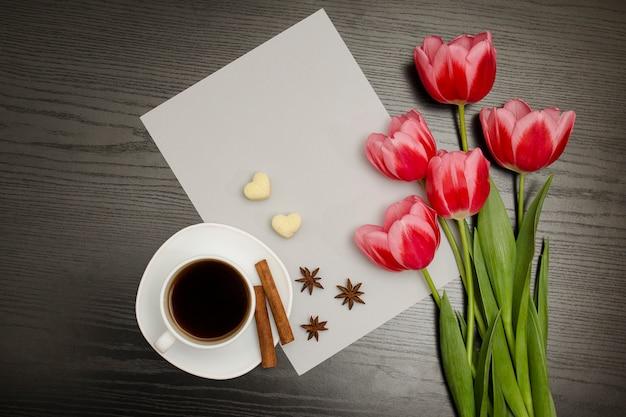 Boeket roze tulpen, een kopje koffie, hartvormige suiker, kaneel, steranijs en vel papier op een zwart hout
