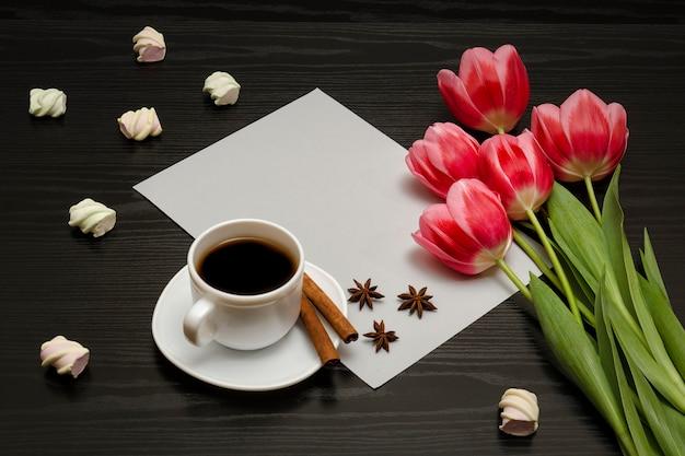 Boeket roze tulpen, een kopje koffie, marshmallow en een vel papier