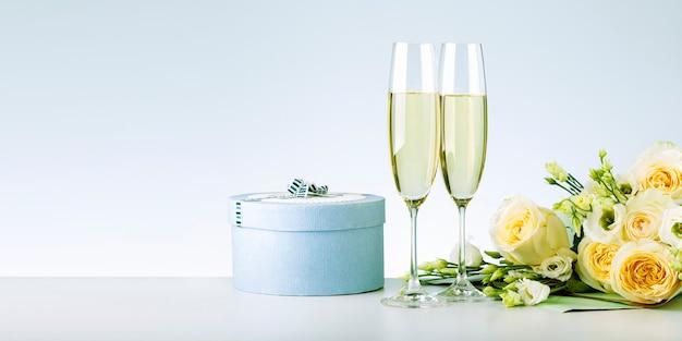 Boeket rozen, champagne en geschenkdoos voor felicitatie.