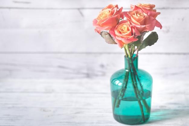 Boeket rozen in de vaas op de houten achtergrond
