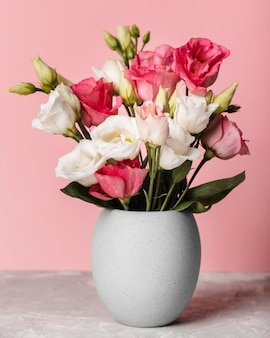 Boeket rozen in een vaas naast een roze muur