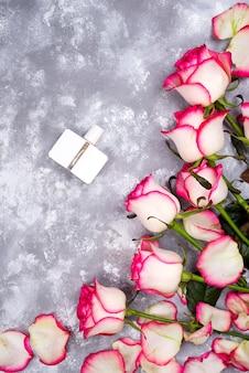 Boeket rozen met parfum op een grijze achtergrond met kopie ruimte