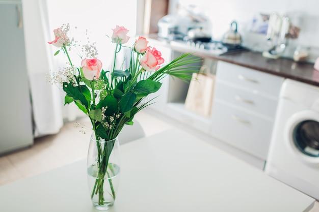 Boeket rozen op keuken. modern keukenontwerp. interieur van keuken versierd met bloemen.