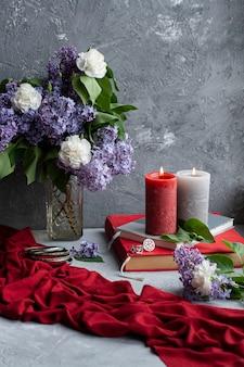 Boeket seringen en anjers, een paar grote kaarsen, boeken en sieraden