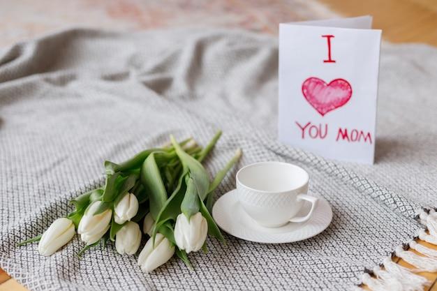 Boeket tulpen, beker, ansichtkaart voor moeder in de woonkamer