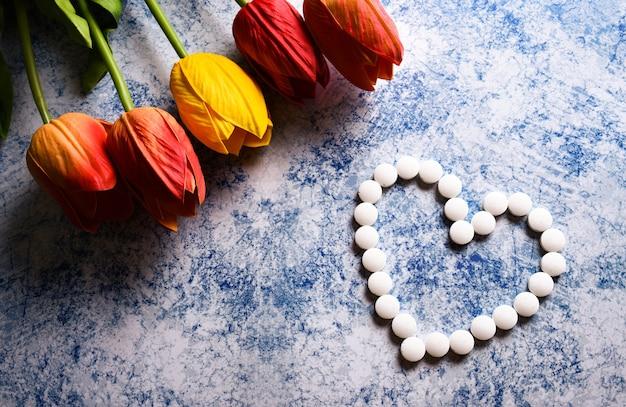 Boeket tulpen en vele witte pillen van hart op een blauwe achtergrond bovenaanzicht