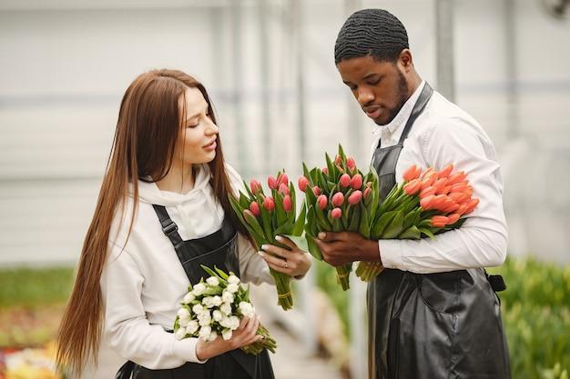 Boeket tulpen in een man. jongen en meisje in een kas. tuinmannen in schorten.