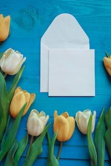 Boeket tulpen met kaart op turquoise rustieke houten tafel. lente bloemen. moederdag .